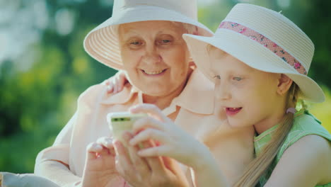 Grandmother-And-Granddaughter-Use-The-Smartphone-Together-Have-A-Rest-In-The-Park-On-A-Summer-Day-4K
