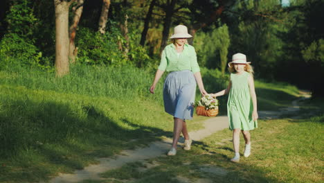 Mom-And-Daughter-Are-Walking-Along-A-Path-In-The-Forest-Carrying-A-Basket-With-Wildflowers-Happy-Par