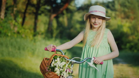 Portrait-Of-A-Blond-Girl-With-A-Bicycle-With-Her-Basket-Of-Wildflowers-Looks-At-The-Camera-4K-Video