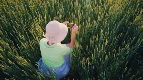 A-Female-Farmer-Is-Photographing-Ears-Of-Green-Wheat-Using-A-Smartphone-Organic-Agriculture-Concept-