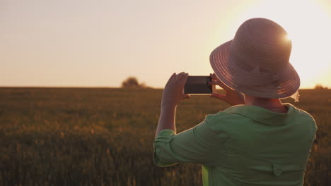 A-Woman-In-A-Hat-Takes-Pictures-Of-A-Beautiful-Sunset-Over-The-Wheat-Field-Organic-Farming-Concept-4