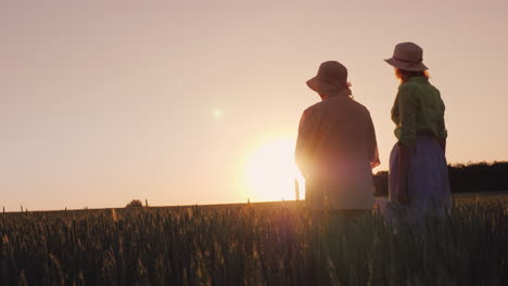 Two-Women---Mother-And-Daughter-Look-At-The-Beautiful-Sunset-Over-The-Wheat-Field
