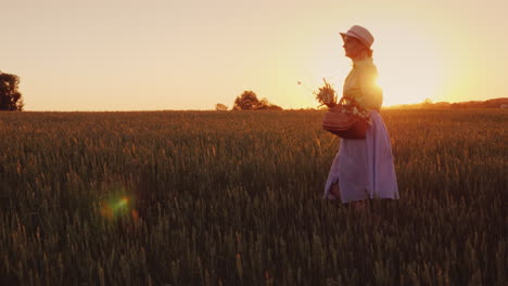 Romantic-Woman-With-Bouquet-Of-Wildflowers-Walking-On-The-Field-At-Sunset-Back-View-4K-Video