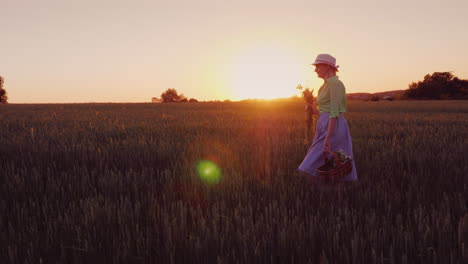 A-Happy-Carefree-Woman-With-A-Basket-Of-Wildflowers-Walks-At-Sunset-In-A-Picturesque-Place-4K-Video