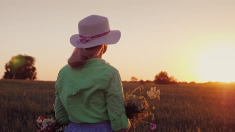 A-Romantic-Woman-With-A-Hat-And-A-Bouquet-Of-Wildflowers-Admires-The-Sunset-Over-The-Wheat-Field
