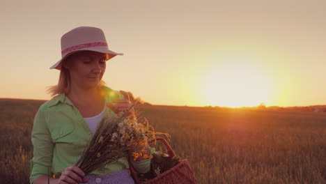 Woman-In-A-Hat-With-A-Bouquet-Of-Wild-Flowers-Walking-Around-The-Field-At-Sunset-4K-Video