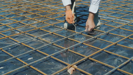 The-Worker-Skillfully-Connects-The-Bars-Of-The-Armature-With-Wire-Preparation-For-Pouring-Concrete-I