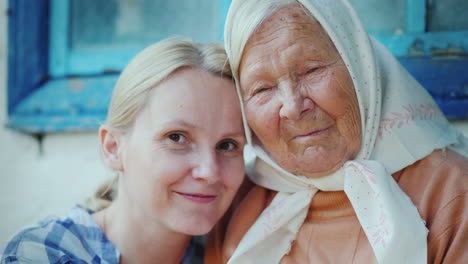 Portrait-Of-An-Elderly-Woman-With-Her-Granddaughter-They-Embrace-They-Look-At-The-Camera-A-Few-Gener