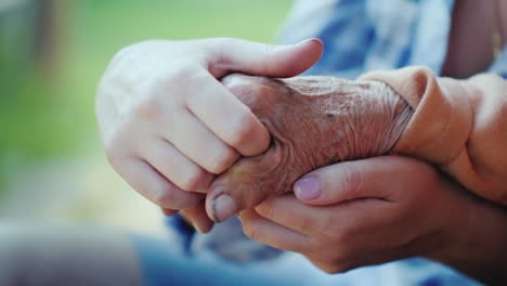 A-Young-Woman-Holds-An-Elderly-Lady's-Hand-Close-Up-Video