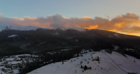 Aerial-View-Of-Mountains-And-Forest-Covered-With-Snow-At-Sunset-In-Winter-2