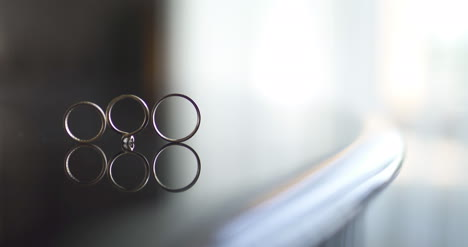 Close-Up-Of-Wedding-Rings-On-Table