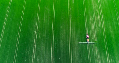 Aerial-Shot-Of-Tractor-Spraying-Field-With-Chemicals-