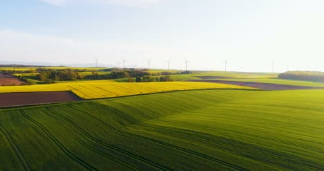 Aerial-View-Of-Summer-Countryside-With-Wind-Turbines-And-Agricultural-Fields-