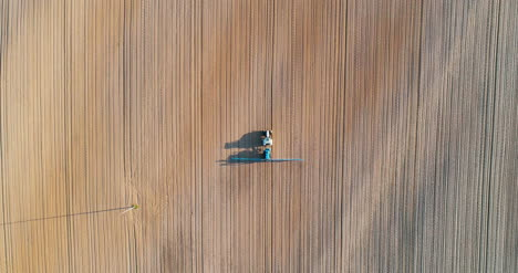 Agricultural-Tractor-Working-In-Field-Drone-View-