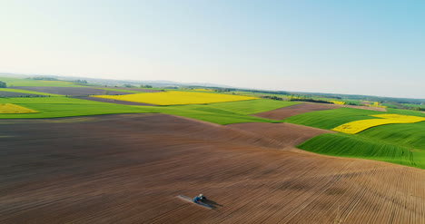 Drone-View-Of-Agricultural-Tractor-Spraying-Field-