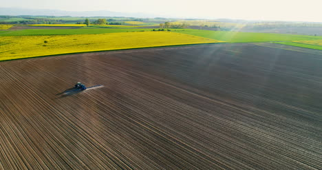 Drone-View-Of-Agricultural-Tractor-Spraying-Field-1