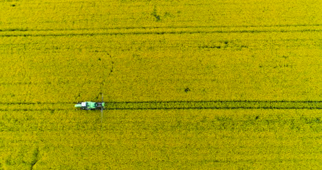 Agriculture-Aerial-Of-Tractor-Spraying-Farm-Land-With-Pesticides