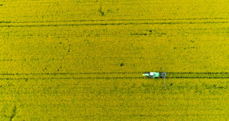 Agriculture-Aerial-Of-Tractor-Spraying-Farm-Land-With-Pesticides-1