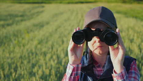 A-Woman-Looks-Through-Binoculars-Standing-In-The-Endless-Green-Field