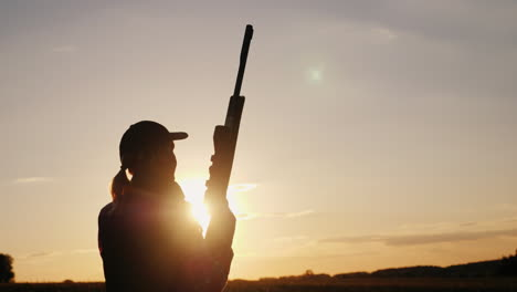 Silhouette-Of-A-Woman-With-A-Rifle-In-The-Rays-Of-A-Sunset-Sports-Shooting-4K-Video