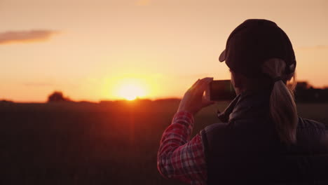 Young-Woman-Farmer-Photographing-A-Beautiful-Sunset-Over-A-Wheat-Field-4K-Video