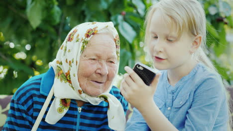 The-Girl-Shows-Grandmother-Photos-On-Her-Smartphone-Communion-Of-Generations-Concept-4K-Video