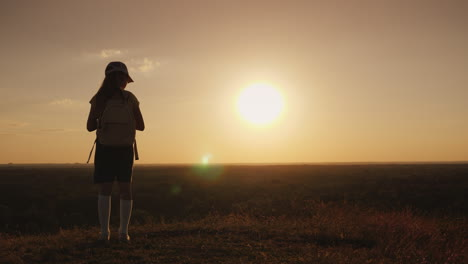 A-Girl-With-A-Backpack-Is-In-A-Picturesque-Place-Looking-Forward-To-The-Sunset-A-Little-Traveler-And