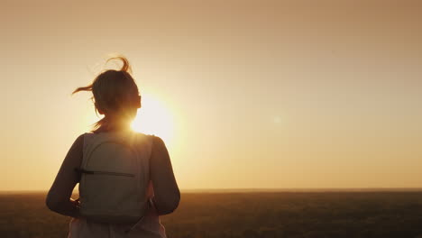A-Young-Woman-With-A-Backpack-Runs-Forward-Towards-The-Sun-Hair-Glows-In-The-Rays-Of-Sunset-Slow-Mot