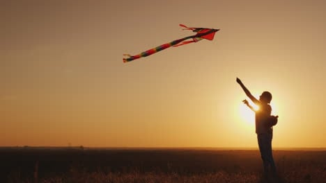 Woman-With-A-Children-s-Backpack-Behind-Her-Back-Runs-A-Kite-At-Sunset-Dream-And-Return-To-Childhood