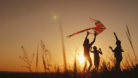 Happy-Family-Playing-With-A-Kite-At-Sunset-Mom-Dad-And-Daughter-Are-Happy-Together-4K-Video