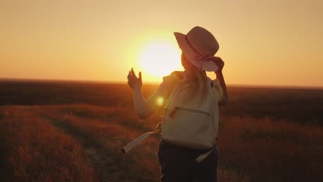 Funny-Girl-In-A-Straw-Hat-Runs-Down-The-Hill-At-Sunset-Holds-The-Hat-With-His-Hands-Leto-And-The-Vac