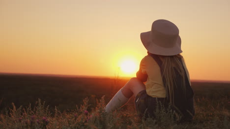 A-Girl-In-A-Hat-Admires-The-Sunset-In-A-Picturesque-Place-She-Sits-On-A-Hill-Her-Chin-On-Her-Hands-B