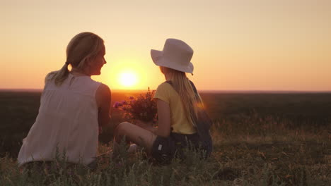 Mom-And-Little-Daughter-Are-Sitting-On-A-Hill-Admiring-The-Sunset-In-The-Hands-Of-Wild-Flowers-Summe
