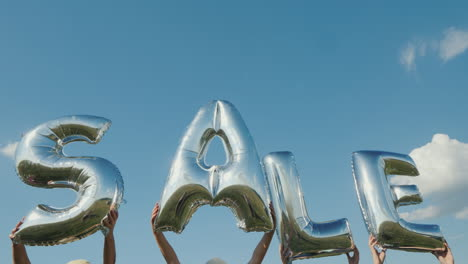 Several-People-Hold-Balloons-In-The-Form-Of-Letters-Make-Up-The-Word-Sale-4K-Video