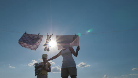 My-Daughter-Helps-My-Mother-To-Hang-Clothes-On-A-Rope-For-Drying-Time-Together-With-Children-Help-To