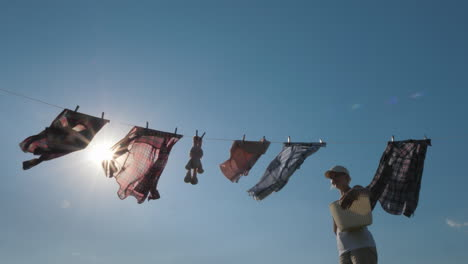A-Woman-With-A-Basket-Looks-Like-Hanging-Wet-Clothes-On-A-Rope-4K-Video