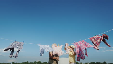 The-Girl-Helps-Her-Grandmother-Hang-Clothes-For-Drying-On-A-Clear-Summer-Day-Against-A-Blue-Sky