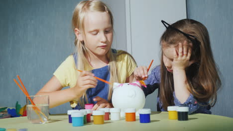 Two-Girls-Paint-A-Piggy-Bank-Together-Having-Fun-Together-Friends-Playing-At-Home-4K-Video