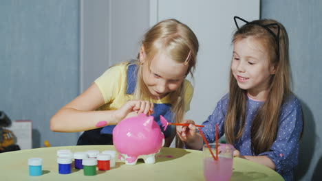 Two-Girls-Girlfriends-Paint-A-Piggy-Bank-Together-Have-Fun-4K-Video
