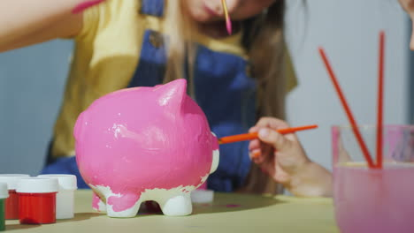 Children-Paint-The-Piggy-Bank-With-Pink-Paint-In-The-Frame-Are-Visible-Only-Hands