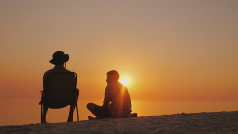 Two-Teenagers-Are-Fishing-On-The-Shore-Of-The-Lake-Chatting-Having-A-Good-Time-Outdoors