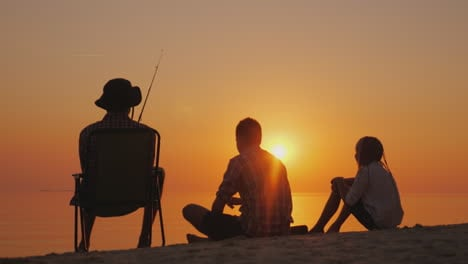 Three-Teenagers-Are-Fishing-On-The-Shore-Of-The-Lake-At-Sunset-Happy-Childhood-Concept-4K-Video