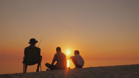 Three-Children-Rest-On-The-Shore-Of-The-Lake-They-Are-Fishing-Recreation-In-The-Fresh-Air-And-Live-C