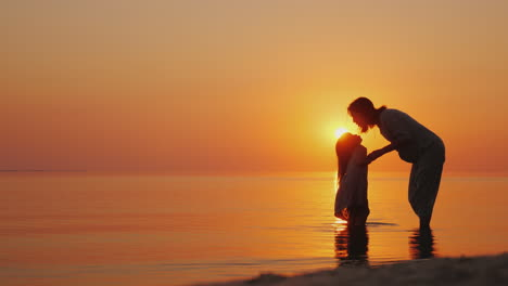 A-Pregnant-Woman-Gently-Kisses-Her-Eldest-Daughter-Beautiful-Silhouettes-Near-The-Sea-At-Sunset-Wait
