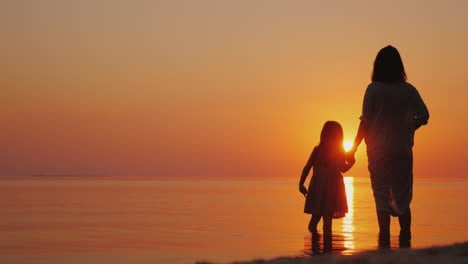 Silhouette-Of-A-Pregnant-Woman-With-A-Baby-Near-By-Stand-Near-The-Sea-At-Sunset-Waiting-For-The-Seco