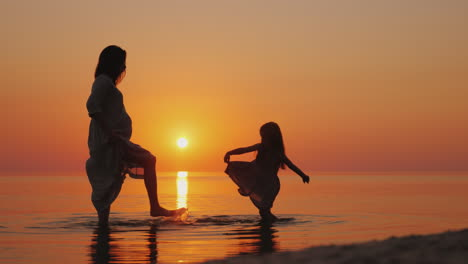 Pregnant-Woman-With-Her-Daughter-Having-Fun-On-The-Beach-Splashing-Water-On-Each-Other-Waiting-For-T