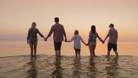 A-Group-Of-Friends-With-Children-Having-Fun-By-The-Water-Holding-Hands-Walking-On-The-Water-Towards-