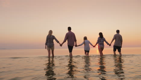 Parents-With-Children-Have-Fun-In-The-Water-Beautiful-Sunset-Over-The-Sea