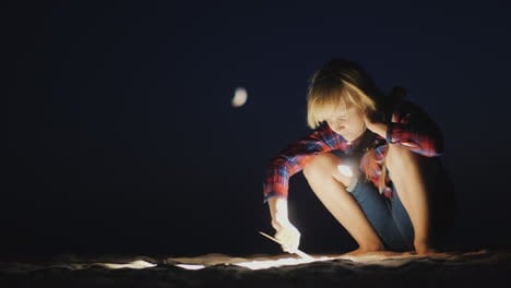 A-Girl-With-A-Flashlight-In-Her-Hand-Is-Looking-For-Something-On-The-Beach-In-The-Dark-Research-And