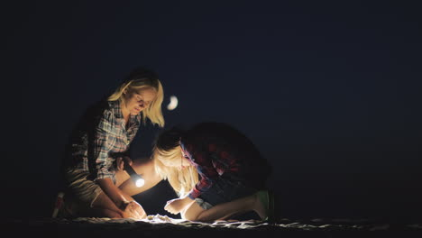 Mom-And-Daughter-Are-Playing-Together-In-The-Sand-At-Night-They-Shine-With-A-Flashlight-Looking-For-